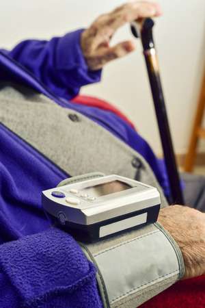 sphygmomanometer: measuring the blood pressure to an old caucasian man with an electronic sphygmomanometer Stock Photo