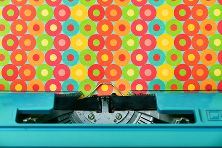 transcription: closeup of a colorful patterned paper in an old blue typewriter