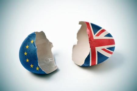 de twee helften van een gebarsten eierschaal, een patroon met de vlag van de Europese Gemeenschap en de andere een patroon met de vlag van het Verenigd Koninkrijk Stockfoto