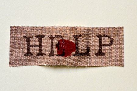adhesive bandage: closeup of a fabric adhesive bandage with a blood stain and the text help, on an off-white background