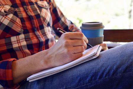 prose: closeup of a young caucasian man wearing jeans and a plaid shirt writing with a pen in a notebook