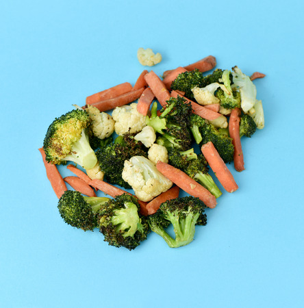 sautee: high-angle shot of some different sauteed vegetables, such as cauliflower, broccoli and carrot, on a blue background