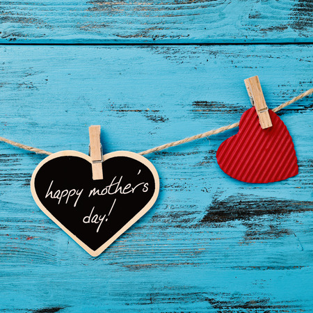 the text happy mothers day written in a heart-shaped chalkboard hanging in a rope with a wooden clothespin next to a red heart, against a blue rustic wooden background
