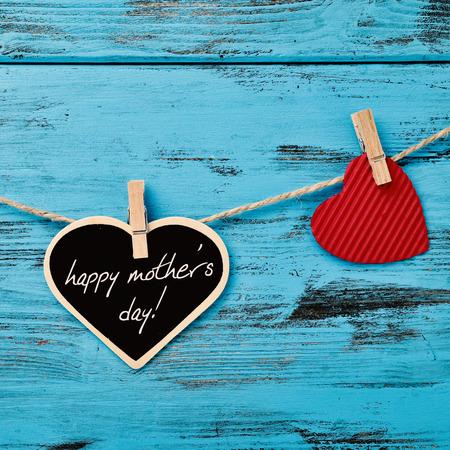 de tekst gelukkige moederdag geschreven in een hartvormig bord opknoping op een touw met een houten wasknijper naast een rood hart, tegen een blauwe rustieke houten achtergrond