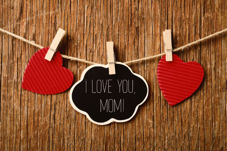clothespegs: the text I love you mom written in a chalkboard in the shape of a thought bubble hanging in a rope with a wooden clothespin next to some red hearts, against a rustic wooden background Stock Photo