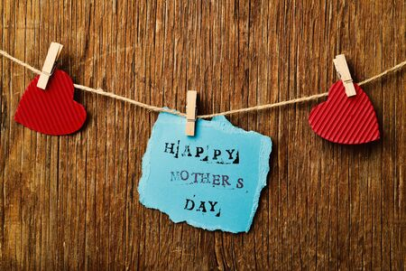 clothespegs: the text happy mothers day written in a piece of blue paper hanging in a rope with a wooden clothespin next to some red hearts, against a rustic wooden background Stock Photo