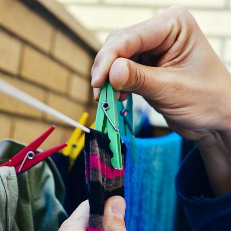Nahaufnahme eines jungen kaukasischen Mannes hängen einige Kleider mit Wäscheklammern in einer Wäscheleine auf