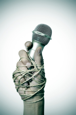 repress: closeup of a microphone in the hand of a young man tied with rope, depicting the idea of the repression of the mass media or the lack of the freedom of speech Stock Photo