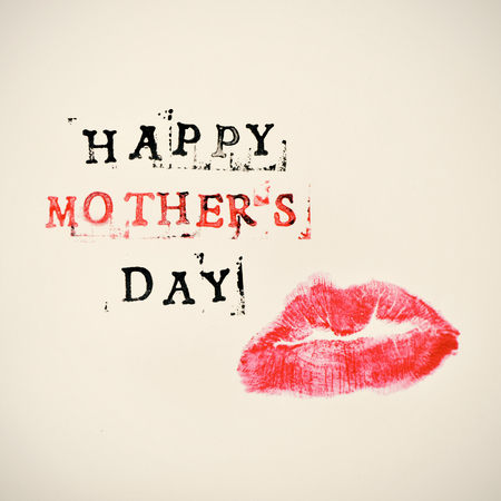 kissing lips: the print of a kiss and the text happy mothers day printed in black and red in a beige gradient background
