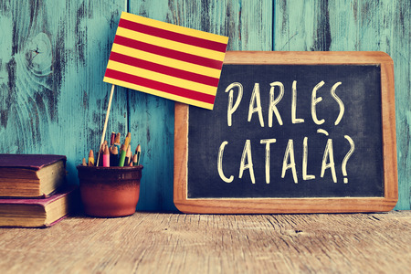 schoolroom: a chalkboard with the question parles catala? do you speak Catalan? written in Catalan, a pot with pencils, some books and the flag of Catalonia, on a wooden desk Stock Photo