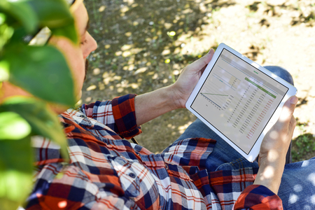 a young farmer man wearing a mustache and a plaid shirt observes some charts in a tablet computer outdoors