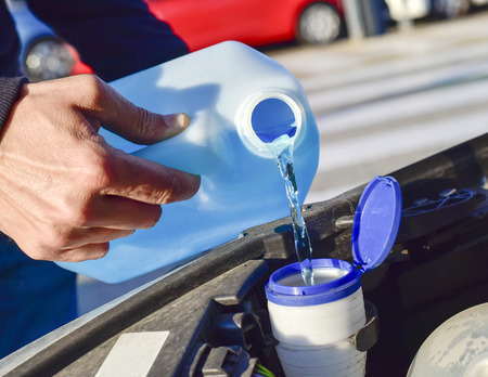 young man filling the tank of windshield washer fluid of a car