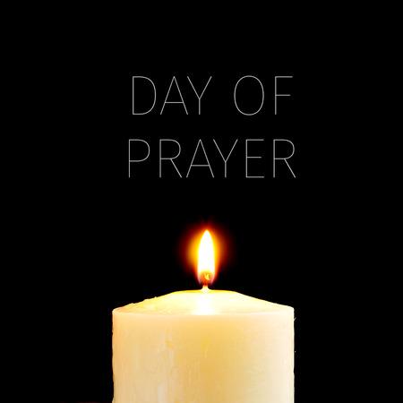 candela: una candela accesa e il giorno testo della preghiera scritta in bianco su uno sfondo nero Archivio Fotografico