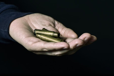 pointed arm: closeup of a young caucasian man with some empty bullets in his hand, against a black background