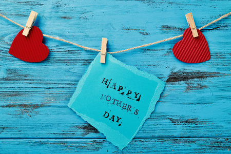 clothespegs: the text happy mothers day written in a piece of blue paper hanging in a rope with a wooden clothespin next to some red hearts, against a rustic blue wooden background Stock Photo