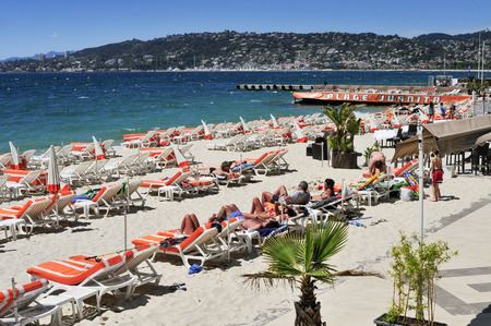 french riviera: Juan-Les-Pins, France - May 15, 2015: People sunbathing in sunloungers on the beach in Juan-Les-Pins, France. Juan-Les-Pins is a well-known summer destination in the French Riviera