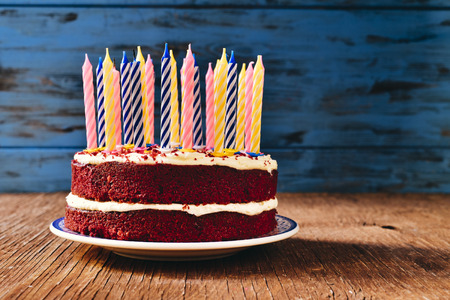 unlit: a red velvet cake topped with some unlit candles on a rustic wooden table Stock Photo
