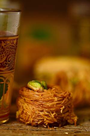 glass topped: closeup of an ornamented glass with tea and a baklava pastry topped with pistachios on a rustic wooden table
