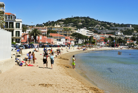 plage: Cannes, France - May 15, 2015: Sunbathers at the Plage du Moure Rouge beach in Cannes, France. This quiet public beach is a bit far from the hustle of the center of Cannes