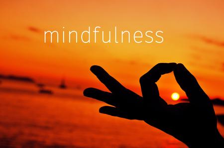 la pleine conscience de texte et un gros plan d'un jeune homme méditant avec sa main dans mudra gyan au coucher du soleil Banque d'images
