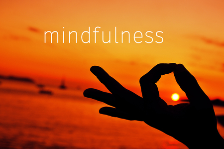 prana: the text mindfulness and a closeup of a young man meditating with his hand in gyan mudra at sunset