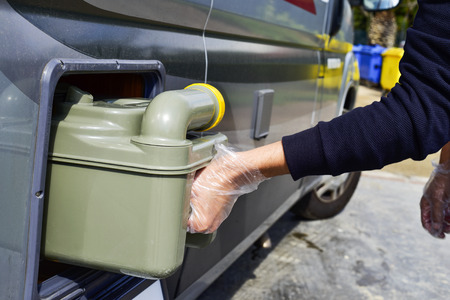 campervan: closeup of a young man removing the sewage tank of a campervan