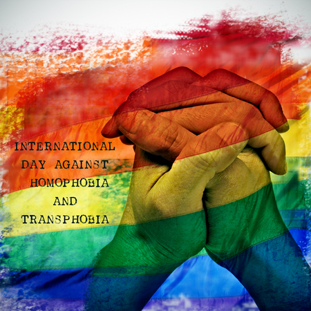 double exposure of a rainbow flag and the hands of a young man put together, and the text international day against homophobia and transphobia Stock Photo