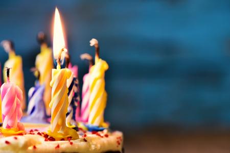 Close-up van sommige onbelichte kaarsen en slechts één verlichte kaars na het uitblazen van de taart Stockfoto
