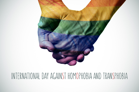 homophobia: closeup of a gay couple holding hands patterned as the rainbow flag and the text international day against homophobia and transphobia Stock Photo