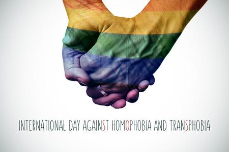 transexual: primer plano de una pareja sosteniendo las manos de los homosexuales modelados como la bandera arco iris y el d�a internacional contra la homofobia texto y la transfobia