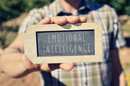 adequacy: closeup of a young caucasian man showing a label-shaped chalkboard with the text emotional intelligence written in it Stock Photo