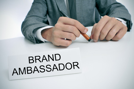 headman: closeup of a young caucasian man wearing a gray suit sitting at his office desk, with a name plate in front of him with the text brand ambassador written in it