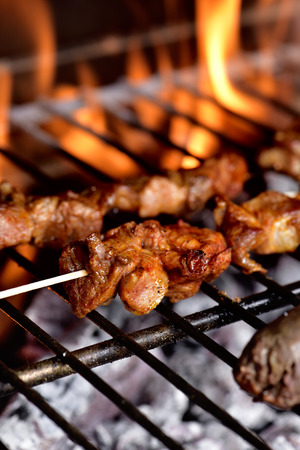 meat skewers: closeup of some meat skewers being grilled in a barbecue