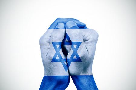 de handen van een jonge man samengevoegd in een patroon met de vlag van Israël, met een klein vignet toegevoegd