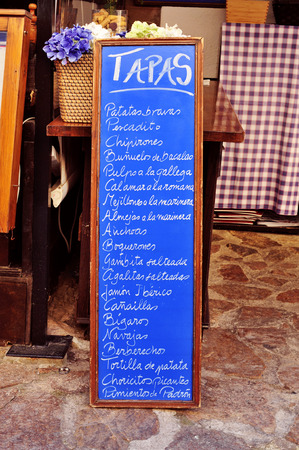 almejas: the chalkboard menu in a restaurant in Spain, with different spanish tapas, such as patatas bravas or tortilla de patatas Stock Photo