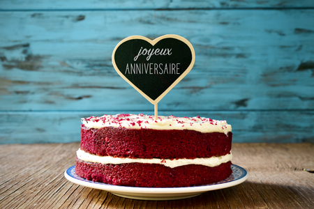 joyeux: a red velvet cake with a heart-shaped chalkboard with the text joyeux anniversaire, happy birthday in french, on a rustic wooden table Stock Photo