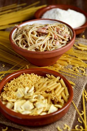 queso rayado: Primer plano de un plato de barro con un poco de pasta sin cocer, un cuenco con espaguetis a la carbonara, y un plato con el queso rallado sobre una mesa Foto de archivo