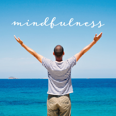 a young caucasian man seen from behind with his arms in the air saluting the new day in front of the sea and the text mindfulness Stock Photo