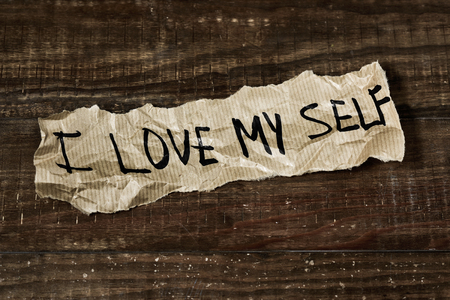 self conceit: the text I love myself written in a piece of paper, placed on a rustic wooden surface
