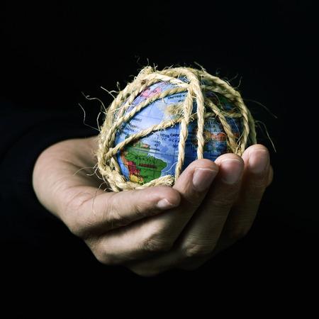 gefesselt: Nahaufnahme von einem jungen Mann mit einer Weltkugel in der Hand mit einem Seil gefesselt, mit einem dramatischen Effekt