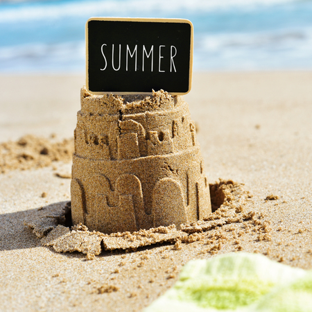 sand mold: closeup of a sandcastle on the sand of a beach topped with a black signboard with the word summer written in it