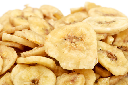 banane: gros plan d'un tas de chips de banane séchées sur un fond blanc