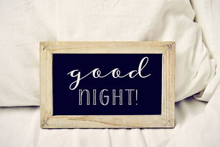 closeup of a wooden-framed chalkboard with the text good night written in it, placed on a comfortable bed Foto de archivo