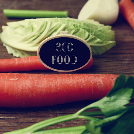 parsnips: closeup of a black signboard with the text eco food placed on a pile of some different raw vegetables, such as carrots, parsnips, turnips, cabbage and celery, on a rustic wooden table