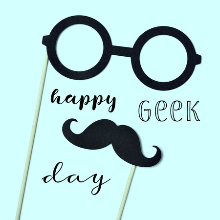 roleplaying: the text happy geek pride and a pair of round-framed eyeglasses and a mustache attached to handles depicting a man face, on a blue background
