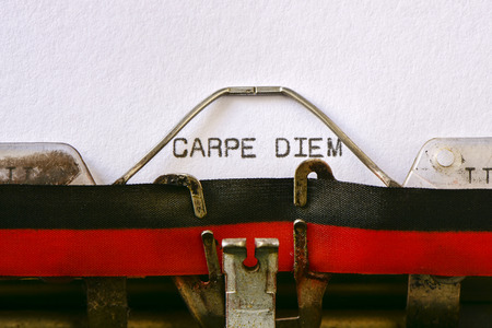carpe diem: closeup of an old typewriter and the text carpe diem typewritten with it in a foil