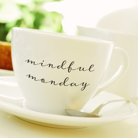 mindful: closeup of a cup of coffee or tea on a set table with the text mindful monday written in it