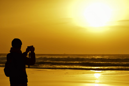 knit cap: the silhouette of a young caucasian man wearing scarf and knit cap taking a picture in front of the sea at dusk, against a colorful orange sky