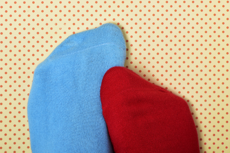 closeup of the feet of someone with a blue sock in one foot and a red sock in the other, on a dot patterned background Stock Photo