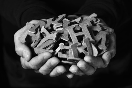 erudition: closeup of the hands of a young man holding a handful of different wooden letters, against a black background, in black and white
